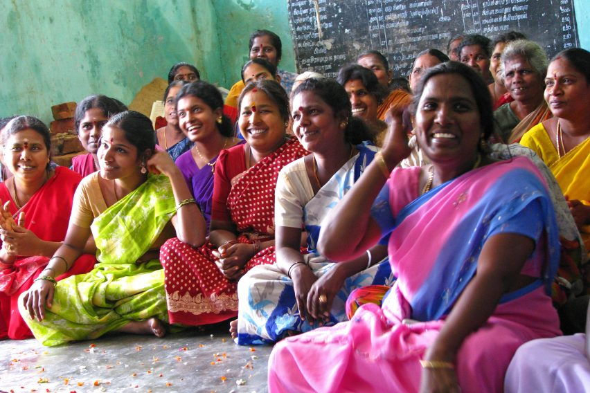 Group of women in India, sitting and smiling
