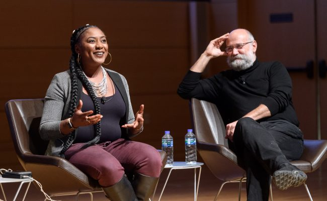 Two panelists on stage, one person is talking while the other is listening and smiling.