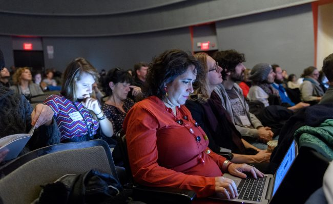 Woman sitting in an auditorium among many other people, looking down at her laptop and working.